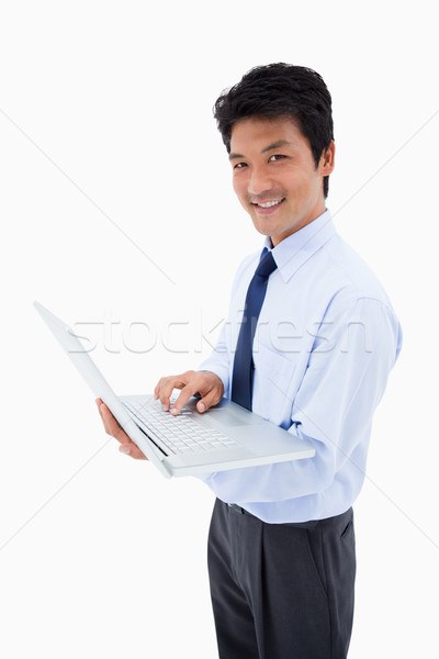 Portrait of a smiling businessman using a laptop against a white background Stock photo © wavebreak_media