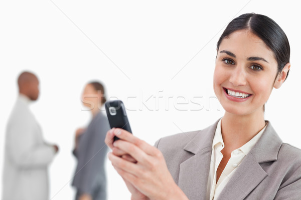Smiling saleswoman holding cellphone with colleagues behind her against a white background Stock photo © wavebreak_media