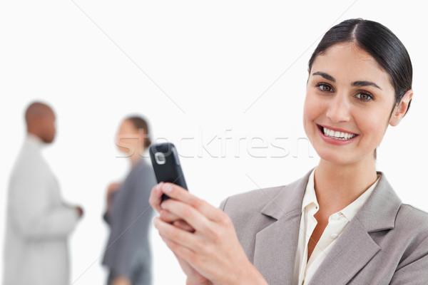 Sonriendo vendedora teléfono celular colegas detrás Foto stock © wavebreak_media