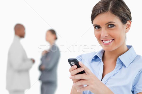 Mosolyog elarusítónő tart mobiltelefon kollégák mögött Stock fotó © wavebreak_media