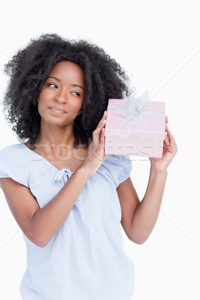 Young woman shaking her gift to guess what it is against a white background Stock photo © wavebreak_media