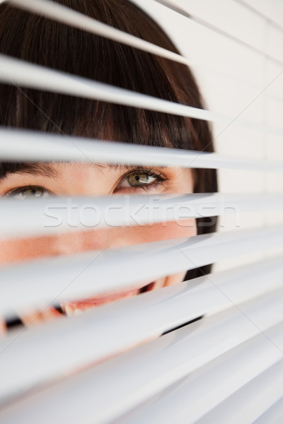 Stock photo: A woman smiling as she glances into the camera through some blinds