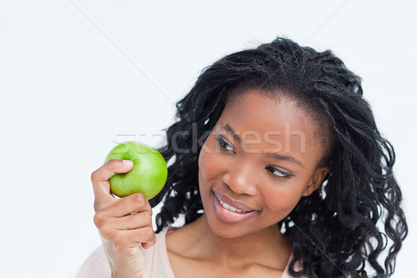 Head shot of a woman who is looking at a green apple she is holding Stock photo © wavebreak_media