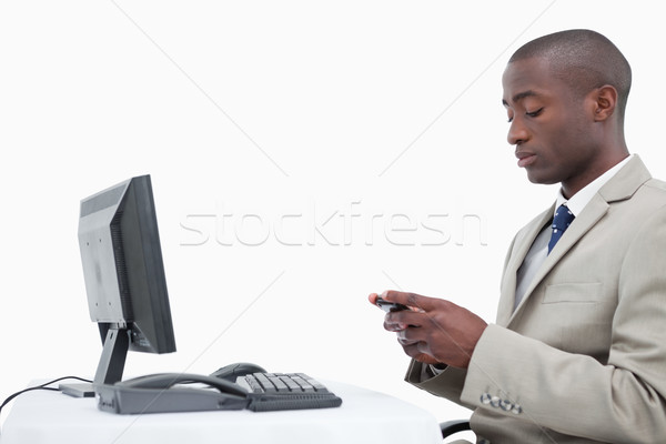 Side view of a businessman sending a text message against a white background Stock photo © wavebreak_media