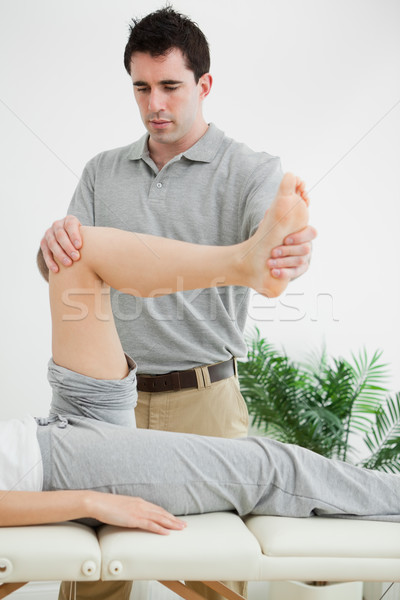 Brunette physiotherapist manipulating a leg in a room Stock photo © wavebreak_media