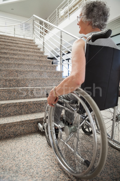 Elderly lady in wheelchair looking up hospital stairs Stock photo © wavebreak_media