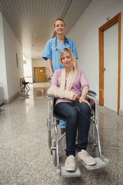 Nurse puching wheelchair of patient with arm sling in hospital corridor Stock photo © wavebreak_media