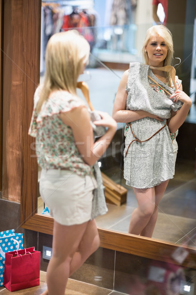 Woman is looking in the mirror at the changing room smiling  Stock photo © wavebreak_media