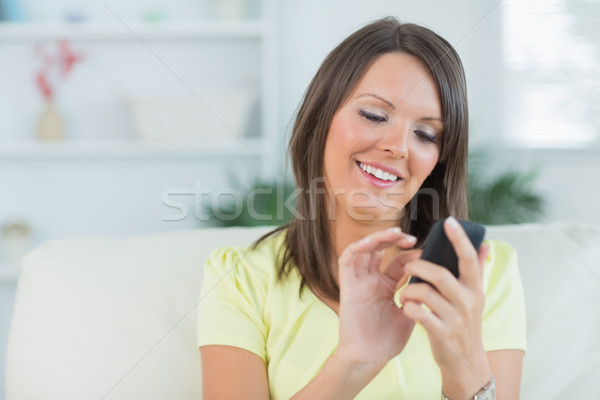 Woman texting with her smartphone in the living room and smiling Stock photo © wavebreak_media