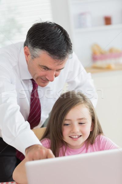 отец указывая что-то ноутбука улыбаясь кухне Сток-фото © wavebreak_media