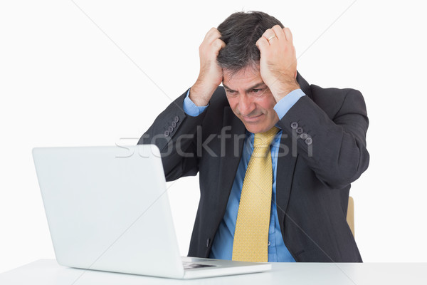 Anxious businessman sitting at his desk with a laptop on a white background Stock photo © wavebreak_media