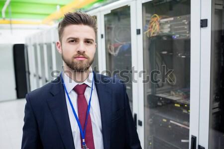 Man looking up thoughtfully into server locker Stock photo © wavebreak_media