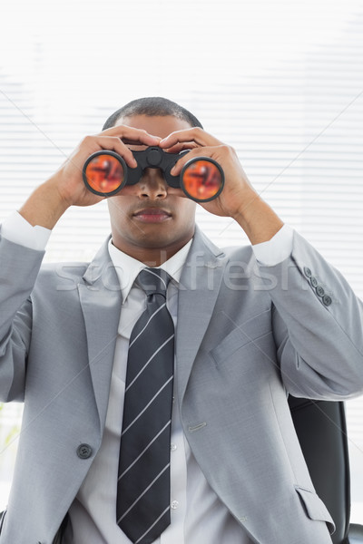 Serious businessman looking through binoculars Stock photo © wavebreak_media