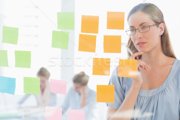 Concentrated artist looking at colorful sticky notes Stock photo © wavebreak_media