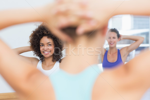 Smiling females with blurred trainer doing stretching exercises Stock photo © wavebreak_media
