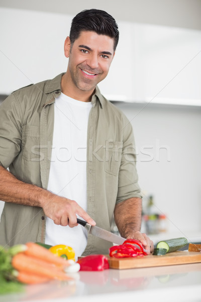 Smiling man chopping vegetables in kitchen Stock photo © wavebreak_media
