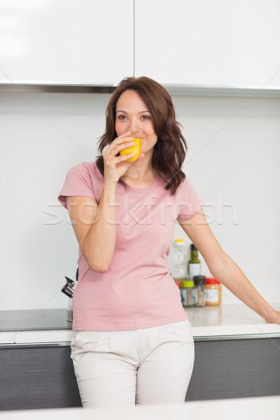 Uśmiechnięta kobieta pitnej sok pomarańczowy kuchnia portret uśmiechnięty Zdjęcia stock © wavebreak_media