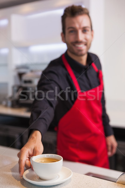 Happy young barista putting cup of coffee down on counter Stock photo © wavebreak_media