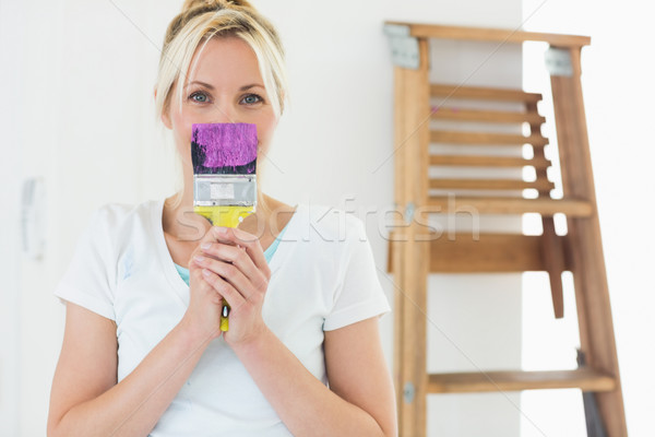 Woman holding paint brush in front of her face at new house Stock photo © wavebreak_media