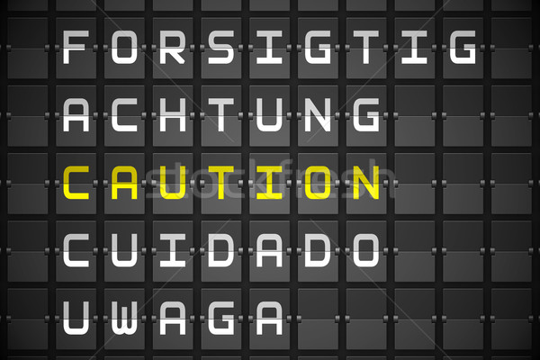 Caution in languages on black mechanical board Stock photo © wavebreak_media