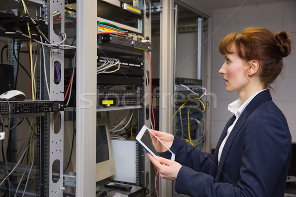Pretty technician using tablet pc while looking at server Stock photo © wavebreak_media