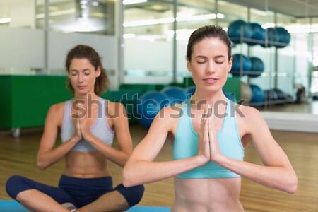 Fit couple sitting in lotus pose in fitness studio Stock photo © wavebreak_media