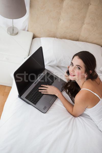 Mooie brunette met behulp van laptop bed home slaapkamer Stockfoto © wavebreak_media