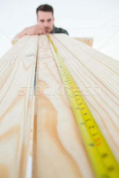 Male carpenter measuring wooden plank Stock photo © wavebreak_media