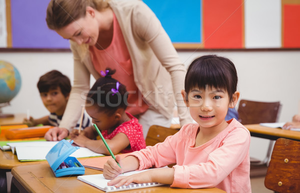 Cute pupil smiling at camera in classroom Stock photo © wavebreak_media