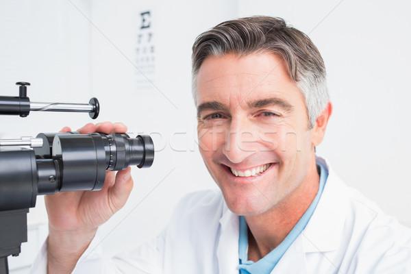 Happy optician using slit lamp in clinic Stock photo © wavebreak_media