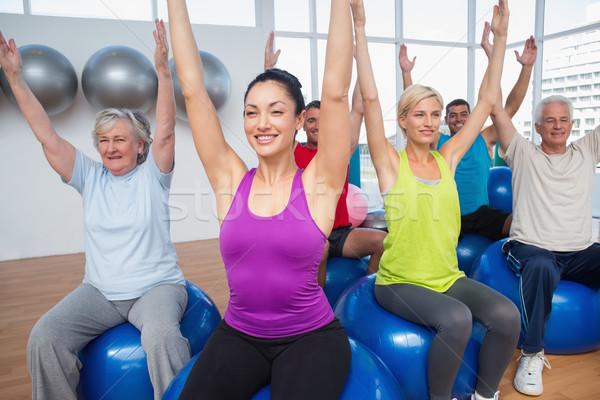 People sitting on exercise balls with hands raised Stock photo © wavebreak_media