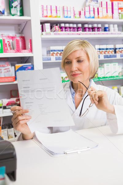 Smiling pharmacist thinking and reading prescription Stock photo © wavebreak_media