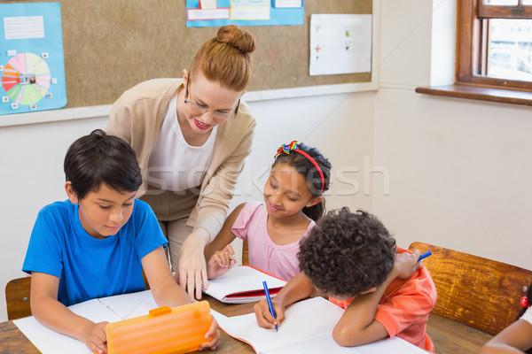 Cute pupils getting help from teacher in classroom  Stock photo © wavebreak_media