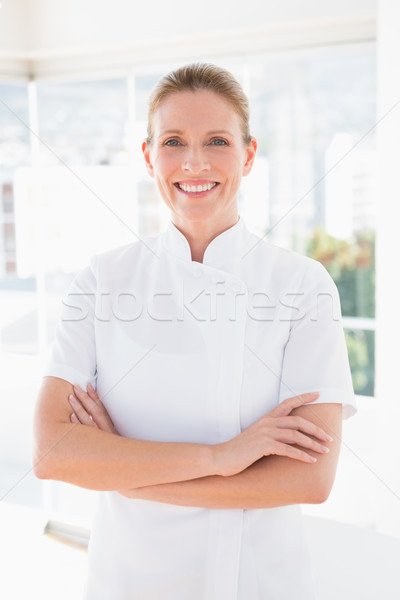Smiling doctor looking at camera with arms crossed  Stock photo © wavebreak_media