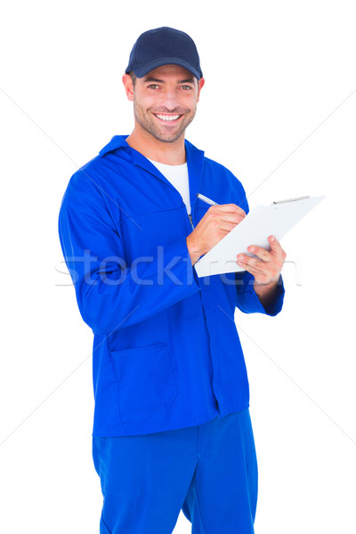 Portrait of happy male mechanic writing on clipboard Stock photo © wavebreak_media