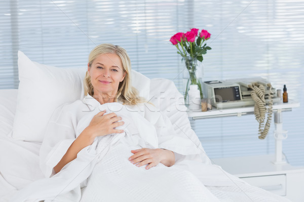 Smiling patient looking at camera on her bed Stock photo © wavebreak_media