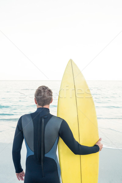 Man in wetsuit with a surfboard on a sunny day Stock photo © wavebreak_media
