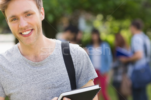 Handsome student smiling at camera outside on campus Stock photo © wavebreak_media