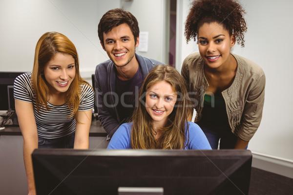 Smiling students using computer together looking at camera Stock photo © wavebreak_media