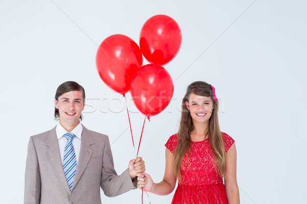 Smiling geeky couple holding red balloons Stock photo © wavebreak_media