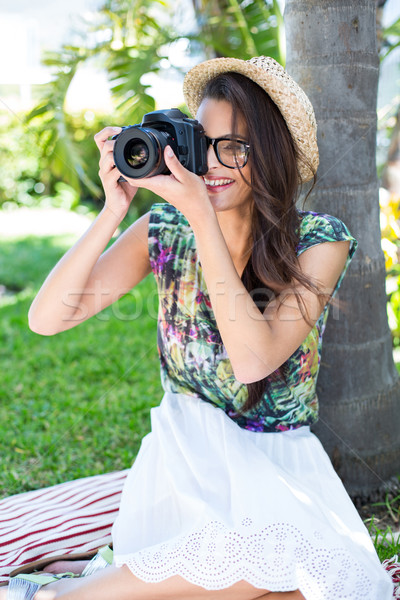 Smiling beautiful brunette sitting on the blanket and taking pic Stock photo © wavebreak_media