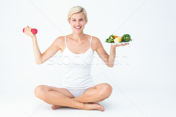 Attractive woman holding vegetables plate and dumbbell Stock photo © wavebreak_media