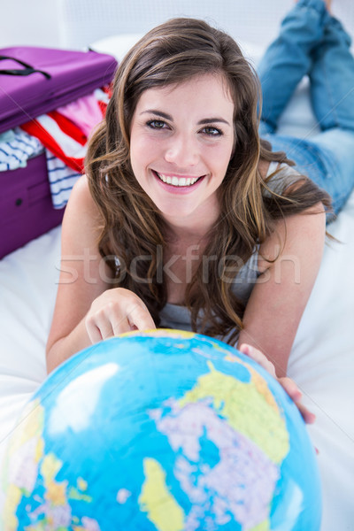Gyönyörű nő bőrönd mutat földgömb otthon hálószoba Stock fotó © wavebreak_media