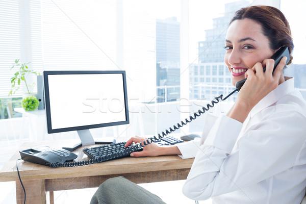 Smiling businesswoman using computer and phoning  Stock photo © wavebreak_media
