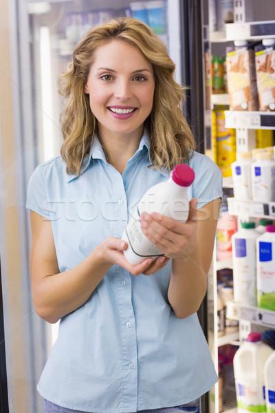 Portrait of a smiling woman having on her hands a milk bottle  Stock photo © wavebreak_media
