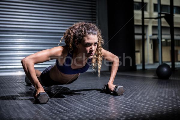 Muscular woman doing push-ups with kettlebells Stock photo © wavebreak_media