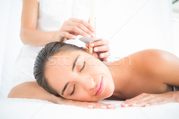 Beautiful woman receiving ear candle treatment at spa center Stock photo © wavebreak_media