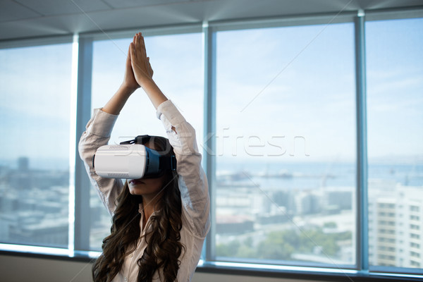 Businesswoman practicing yoga with arms raised while using virtual reality glasses Stock photo © wavebreak_media