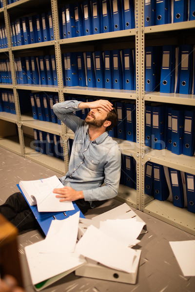 Frustrated businessman with file and papers sitting in storage room Stock photo © wavebreak_media