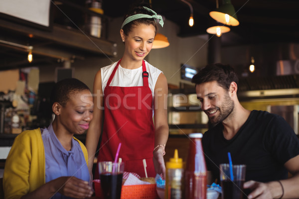 Stock photo: Waitress serving burger and french fries to customer